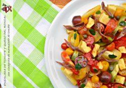 Plato de ensalada de tomate con queso del Roncal, anchoas de Santoña, alcaparras y vinagreta de mermelada de tomate.