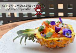 Cóctel de marisco y frutas tropicales presentado en una piña baby.