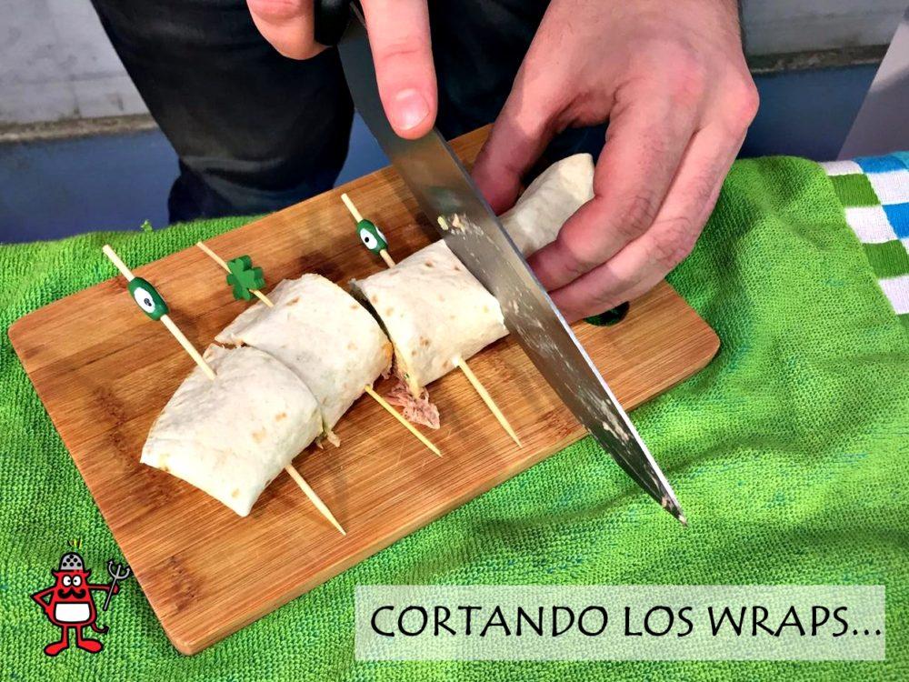 Cortando wraps de hummus, atún y ensalada