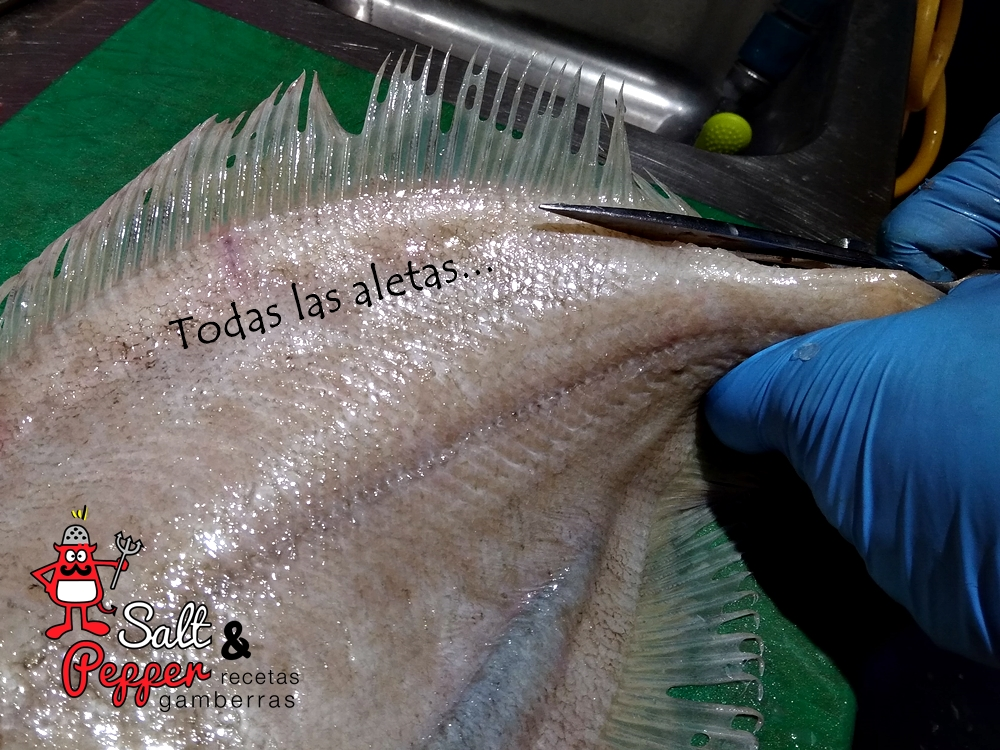 Pescadero retirándole las aletas a un pescado.