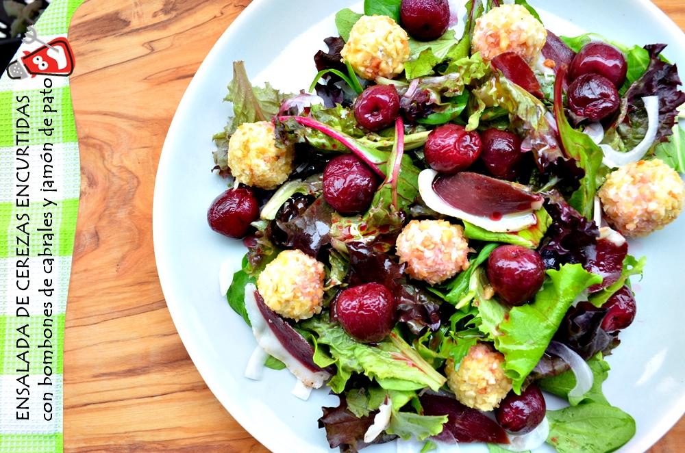 Plato de ensalada de cerezas encurtidas, bombones de cabrales y jamón de pato.